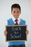 Schoolboy holding writing slate with text back to school against white background Stock Images