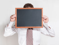 Schoolboy holds empty black chalkboard Royalty Free Stock Images
