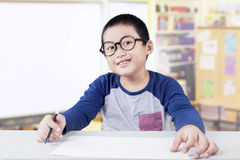 Schoolboy holds marker and empty paper in class Royalty Free Stock Photo