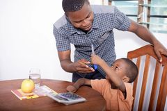 Schoolboy and home teacher 4. The master of the house in his black shirt leaning over the schoolboy`s shoulder, helping him to do his exercises. Now the happy Royalty Free Stock Images