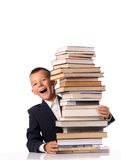 Schoolboy with huge stack of books Royalty Free Stock Image
