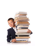 Schoolboy with huge stack of books Royalty Free Stock Photos