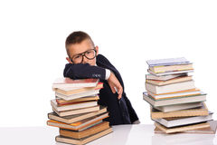 Schoolboy with huge stack of books Royalty Free Stock Photography