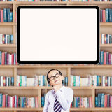 Schoolboy imagine something in library. Thoughtful little boy standing in the library while looking up at empty board Stock Images