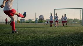 Schoolboy junior league player kicks ball low angle shot. Schoolboy junior league player kicks ball and guys catch at training match low angle shot stock video footage