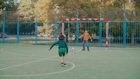 A schoolboy kicks a soccer ball on goal, a second schoolboy catches the ball. A schoolboy kicks a soccer ball on goal. The second student catches the ball on stock video footage