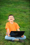 The schoolboy with laptop. The cheerful boy with laptop on green grass Royalty Free Stock Image