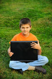 The schoolboy with a laptop. The schoolboy sits and works on the laptop on a green grass outside Royalty Free Stock Images