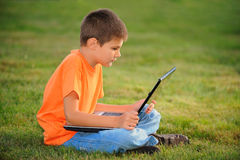 The schoolboy with laptop. The schoolboy sits and works on the laptop on a green grass outside Stock Images