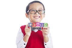 Schoolboy with LEARN word. Portrait of asian elementary school student showing LEARN word. shot in studio isolated on white Stock Images