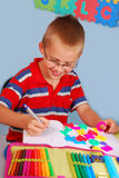 Schoolboy learning to write letters. Schoolboy sitting in the classroom and learning to write letters Stock Photo