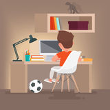 Schoolboy learns lessons at home. Boy reading while sitting at y Stock Image
