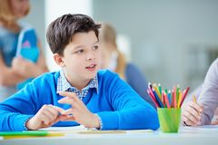 Schoolboy at lesson. Portrait of cute schoolboy sitting at lesson on background of his classmates Royalty Free Stock Photography