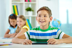 Schoolboy at lesson. Portrait of smart lad at workplace looking at teacher with his classmates on background Stock Image