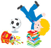 Schoolboy after lessons. Schoolkid balancing on his hands on a pile of books Royalty Free Stock Image