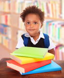 Schoolboy in library. Portrait of little African schoolboy sitting in library and reading different colourful books, doing homework, back to school concept stock photos