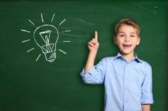 Schoolboy with light bulb. Schoolboy standing near blackboard with light bulb Stock Image