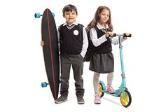 Schoolboy with a longboard and a schoolgirl with a scooter Royalty Free Stock Photos