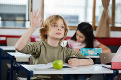 Schoolboy Looking Away While Raising Hand At Desk. Cute schoolboy looking away while raising hand at desk with female classmate in background Royalty Free Stock Photography