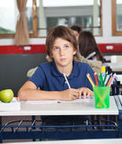 Schoolboy Looking Away While Writing At Desk Stock Image