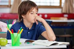 Schoolboy Looking At Book In Classroom Royalty Free Stock Photography