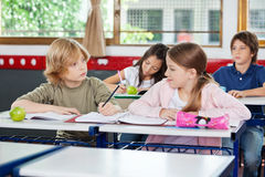 Schoolboy Looking At Girl While Writing At Desk Stock Images