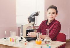 Schoolboy looking in microscope on lesson. Smiling schoolboy studying with microscope during lesson of chemistry or biology in school and looking at the camera stock photo