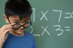 Schoolboy looking over spectacle in a classroom. Front view of Asian schoolboy looking over spectacle in a classroom at elementary school stock photo