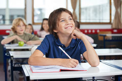 Schoolboy Looking Up While Studying At Desk. Happy young schoolboy looking up while studying at desk with friends in background Stock Image
