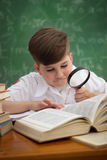 Schoolboy looks through a magnifying glass in book Stock Image