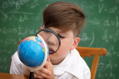 Schoolboy with loupe Stock Images