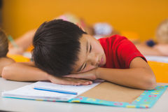 Schoolboy lying on desk in classroom Royalty Free Stock Photos