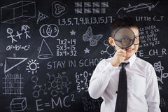 Schoolboy with magnifier and doodles Stock Photography