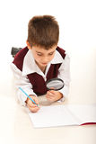 Schoolboy with magnifier home Royalty Free Stock Images