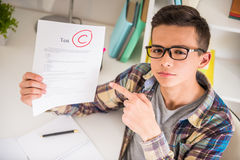 Schoolboy. Male teenager sitting at the table at home and showing bad test results stock photos