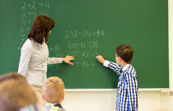 Schoolboy with math teacher writing on chalk board. Education, elementary school, learning, math and people concept - close up of little schoolboy with teacher royalty free stock image