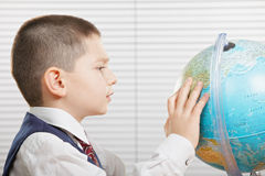 Schoolboy med jordklotet Arkivbild
