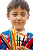 Schoolboy med kulöra blyertspennor Royaltyfri Bild