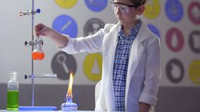 Schoolboy mixes orange liquid in flask in laboratory. Young chemist works in laboratory. The boy in protective glasses mixes orange liquid in a flask. Chemical stock video footage