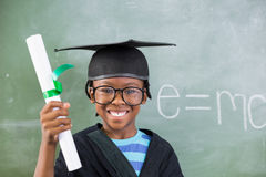 Schoolboy in mortar board holding certificate in classroom. Portrait of schoolboy in mortar board holding certificate in classroom at school Stock Photography