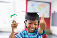 Schoolboy in mortar board holding certificate in classroom. Portrait of schoolboy in mortar board holding certificate and showing thumbs up in classroom at Stock Images