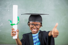 Schoolboy in mortar board holding certificate and showing thumbs up in classroom. Portrait of schoolboy in mortar board holding certificate and showing thumbs up Royalty Free Stock Photos
