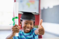 Schoolboy in mortar board holding certificate and showing thumbs up in classroom. Portrait of schoolboy in mortar board holding certificate and showing thumbs up Royalty Free Stock Images