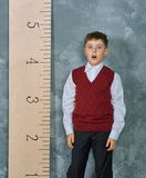 Schoolboy next to the measuring ruler Royalty Free Stock Photos