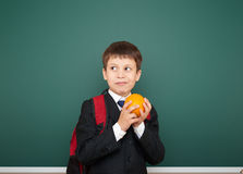 Schoolboy with orange and the school board Stock Photo
