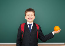 Schoolboy with orange and the school board. Schoolboy with orange near the school board Stock Image