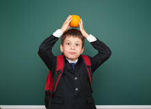 Schoolboy with orange and the school board Royalty Free Stock Photo