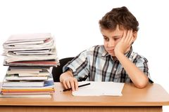 Schoolboy overwhelmed by books. Portrait of a schoolboy overwhelmed by the stack of books on his desk Royalty Free Stock Photo