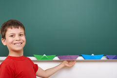 Schoolboy with paper boat play near a blackboard, empty space, education concept Royalty Free Stock Photos