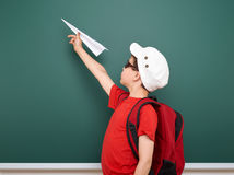 Schoolboy with paper plane play near a blackboard, empty space, education concept Stock Image